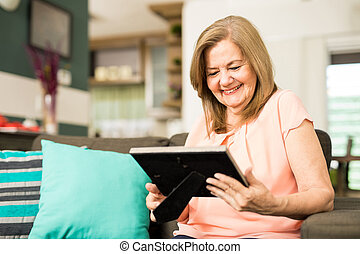 Senior woman staring at photo frame