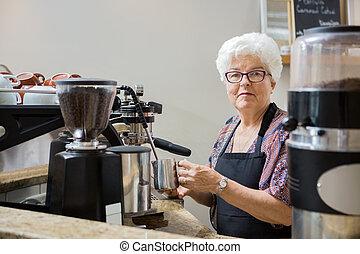 Senior Woman Steaming Milk with Espresso Machine - Portrait...