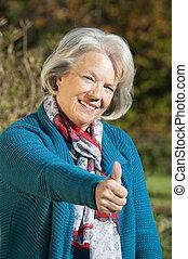 Senior woman holding thumbs up