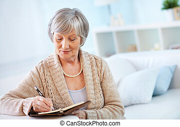 Senior woman making notes in notepad