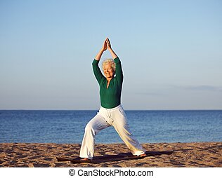 Senior woman stretching against beach background