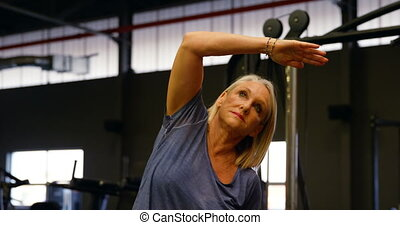 Senior woman stretching in fitness studio 4k
