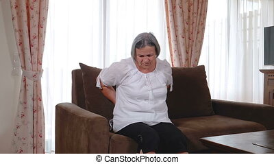 Senior woman suffering from backache at home - Mature woman...