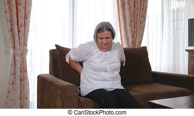 Senior woman suffering from backache at home - Pan of mature...
