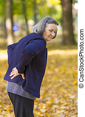Senior woman suffering from backache outdoors