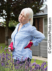 Senior Woman Suffering From Backache Whilst Gardening At Home