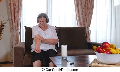 Senior woman suffering from elbow pain at home. Old age, ...