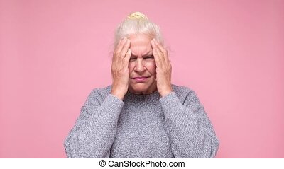 Senior woman suffering from headache desperate and stressed because of pain and migraine. She is holding hands on head.