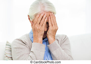 senior woman suffering from headache or grief