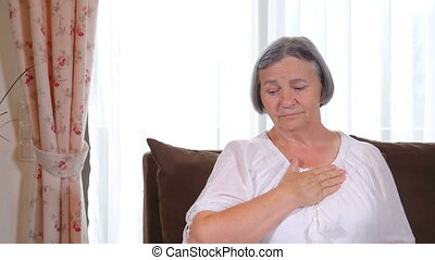 Senior woman suffering from heartache at home - Senior woman...