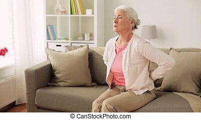 senior woman suffering from pain in back at home - old age,...