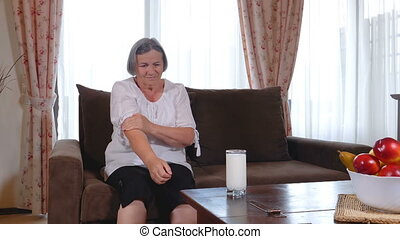 Senior woman suffering from pain in hand at home. Old age,...