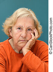 Real senior woman sulking, looking at camera. Much facial details like brown aged spots, wrinkles, no make-up, great color contrast of blue wall and orange shirt.