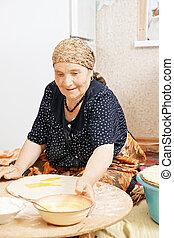 Senior woman taking bowl
