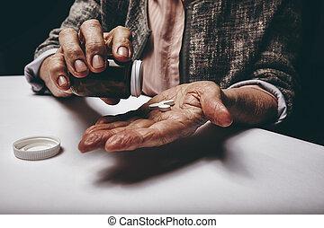 Senior woman taking medicine.