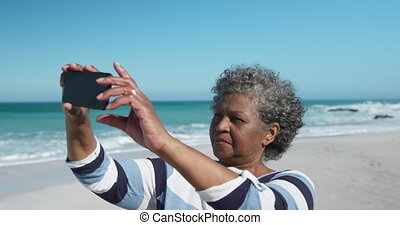 Senior woman taking photos at the beach