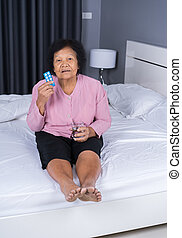 senior woman taking pill with glass of water in bed