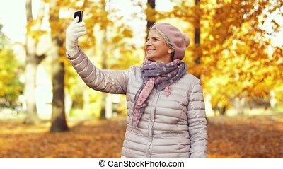 senior woman taking selfie at autumn park