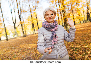 senior woman taking selfie at autumn park