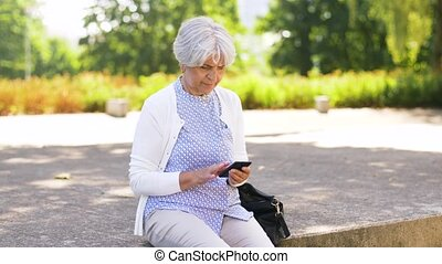 senior woman taking smartphone out of bag in park -...