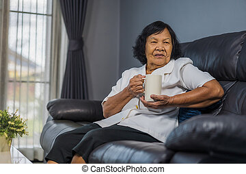senior woman talking and drinking a cup of water