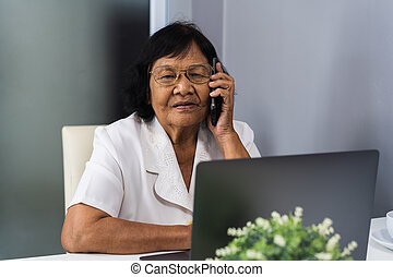 senior woman talking on mobile phone and using laptop