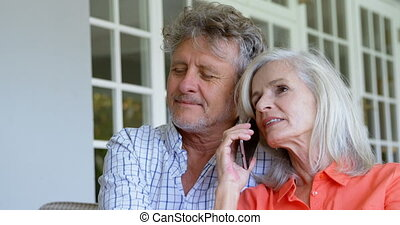 Senior woman talking on mobile phone next to her man on sofa 4k