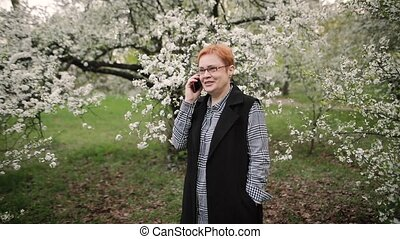 Senior woman talking on smartphone in the garden.