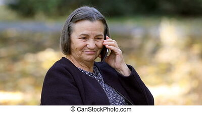 Senior woman talking on smartphone outdoors