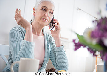 senior woman talking on smartphone with gesture while sitting at table at home