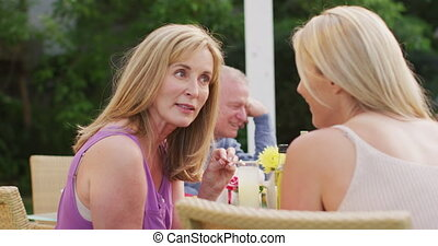 Senior woman talking to young woman while having lunch outdoors