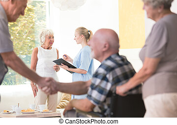 Senior woman talking with nurse