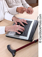 Senior woman tapping a computer keyboard