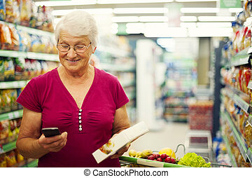 senior woman, texting, képben látható, mobile telefon, -ban, élelmiszer áruház