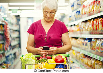 Senior woman texting on mobile phone at supermarket