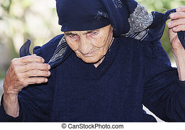 Senior woman ties up head with scarf