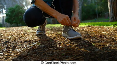 Senior woman tying shoe laces in the park 4k