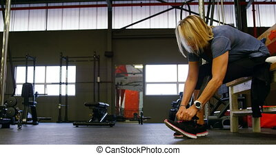 Senior woman tying shoelace in fitness studio 4k - Disabled...