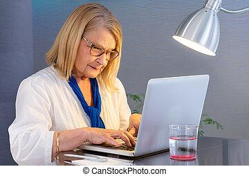 Senior woman typing on laptop at home.