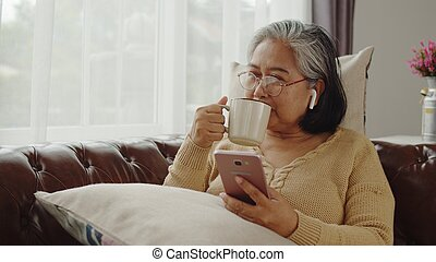 Senior woman use wireless earphone listening music and drink coffee