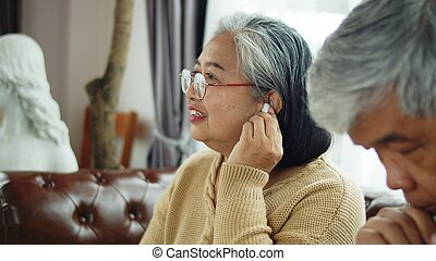 Senior woman use wireless earphone to talking with telephone communication