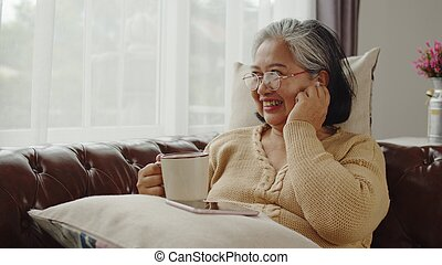 Senior woman use wireless earphone while talking with happiness
