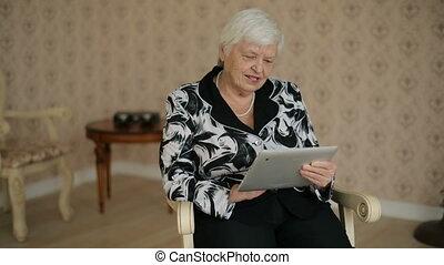 Senior Woman Uses Tablet PC