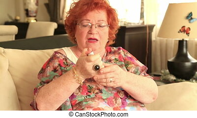 Senior woman using an asthma inhaler - Mature woman using...
