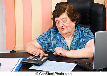 Senior woman using calculator