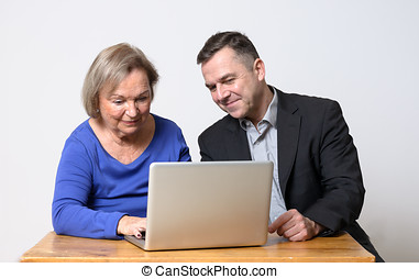 Senior woman using computer beside man in suit