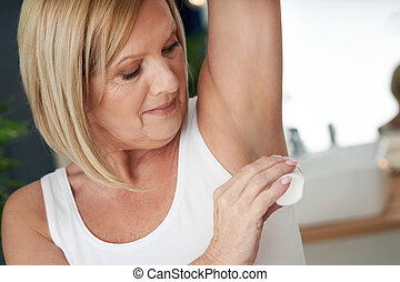Senior woman using deo roll-on in the bathroom