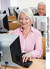 Senior Woman Using Desktop PC In Class