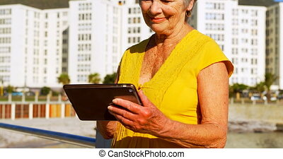 Senior woman using digital tablet at promenade 4k - Senior...