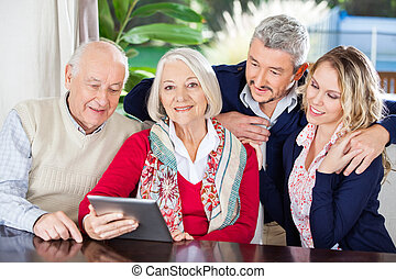 Senior Woman Using Digital Tablet With Family At Nursing Home